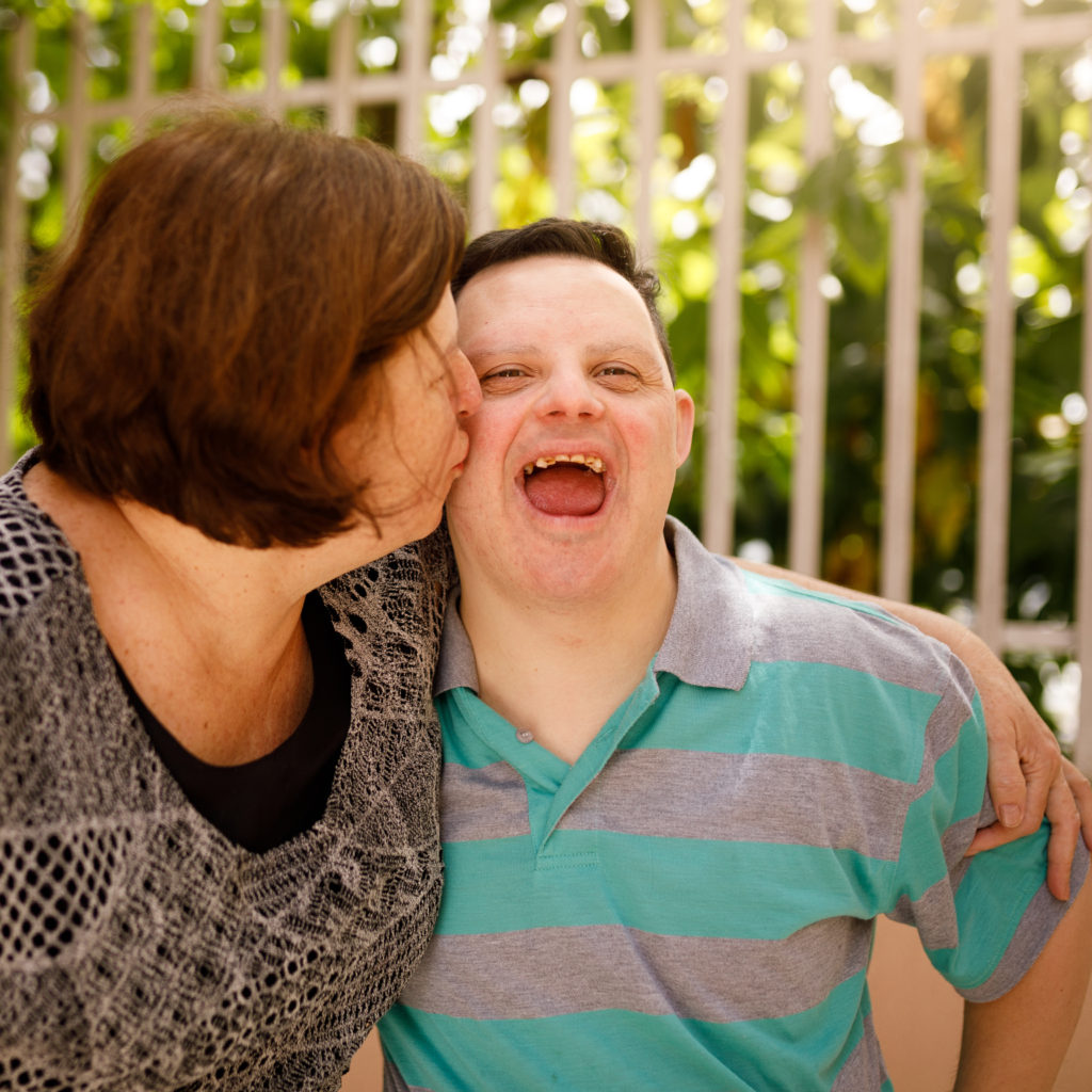 Mother kissing her son with special needs