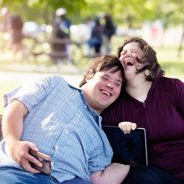 Couple in love of 26 years old Down Syndrome in a park in Montreal doing selfie with mobile phone. They are learning to live independently.