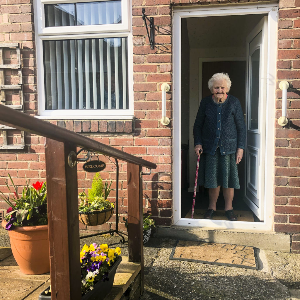 Senior woman standing in her doorway as she keeps her social distance to a minimum while relatives visit.