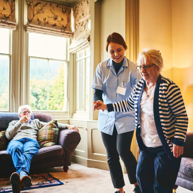 Young female nurse supporting old woman to walk indoors with senior man relaxing on sofa at back