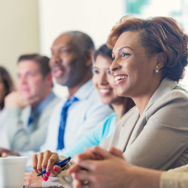 Mid adult African American businesswoman is smiling while attending business conference. She is listening to speaker in seminar while she sits in a row with other diverse professional businesspeople. Woman is wearing business casual clothing and is taking notes. She's drinking a cup of coffee.