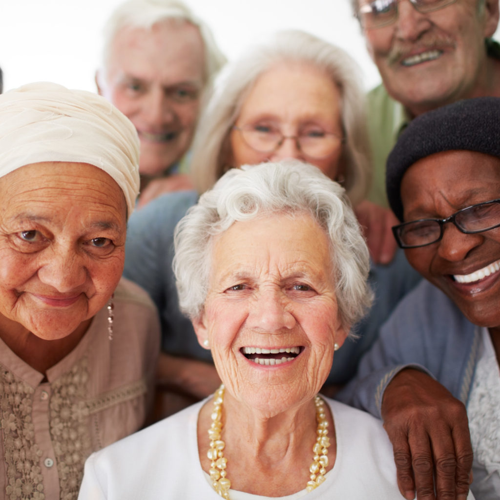 A group of seniors smiling together while in a retirement home